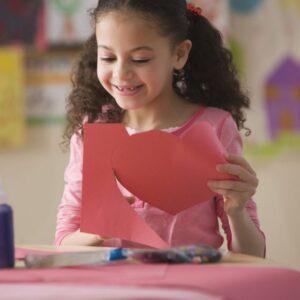 Child making a heart art project