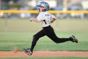 child playing baseball running