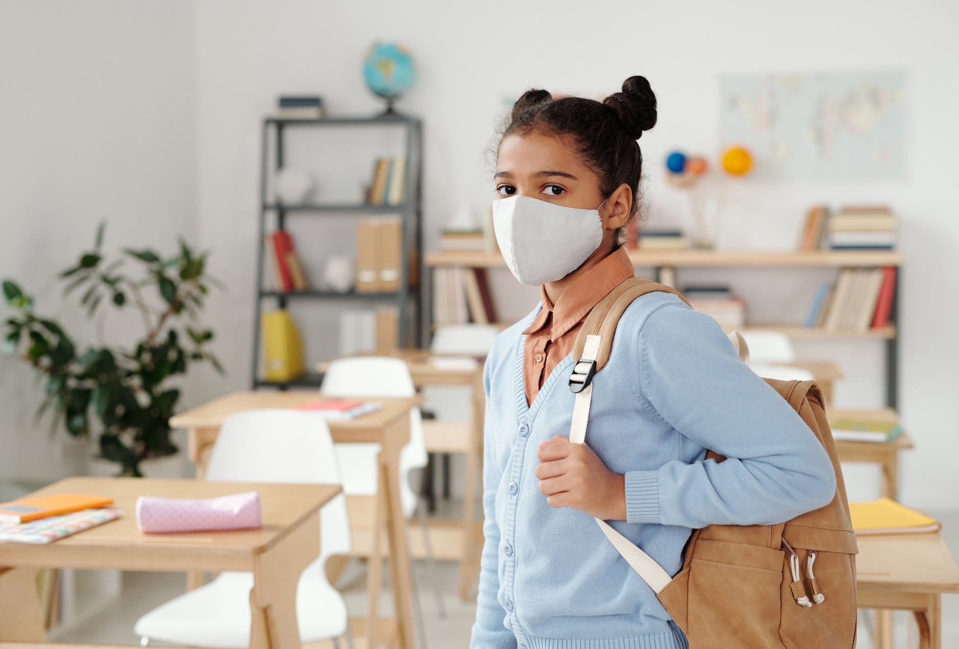 girl in mask going to school